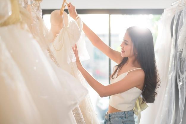 Een jonge mooie bruid die een huwelijksuitrusting kiest bij huwelijksstudio, huwelijksconcept
