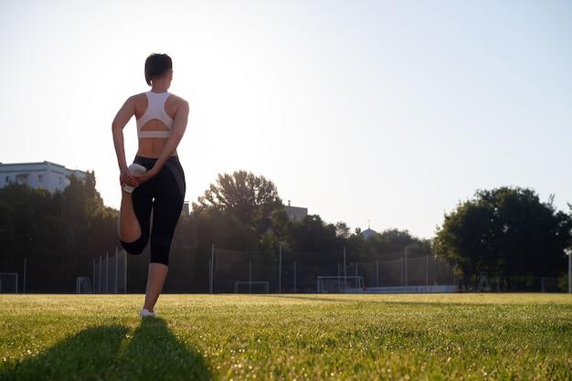 Een jonge, mooie, donkerharige vrouw met een kort kapsel en atletisch gebouwde oefeningen in het park in de vroege ochtend. gezond levensstijlconcept. yoga