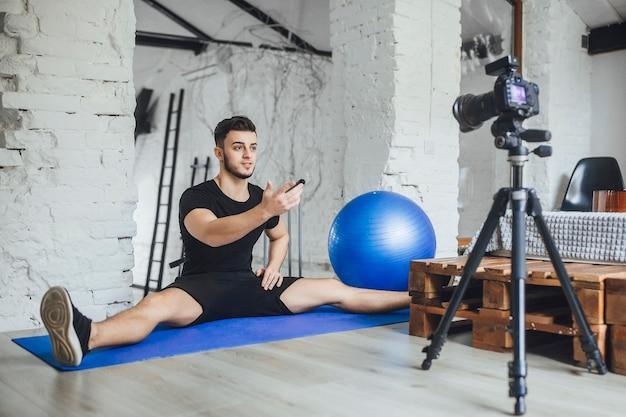 Een jonge, mooie fitnessblogger schrijft video's voor zijn blog en vertelt de basisregels tijdens een training, in een kamer in loftstijl