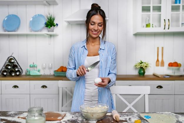 Een jonge mooie huisvrouw staat in de keuken aan tafel en wil een ei snijden met een mes