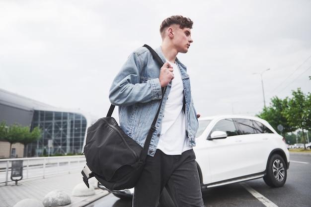 Een jonge mooie man op de luchthaven wacht op de vlucht.