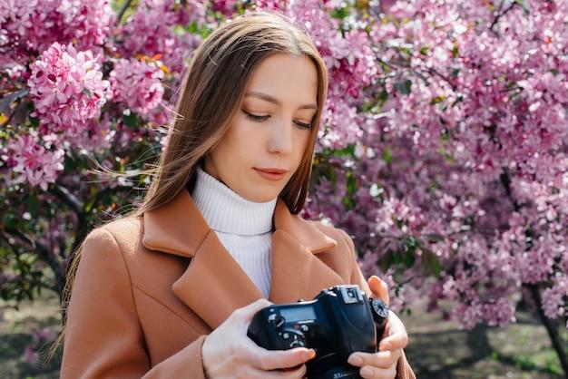 Een jonge mooie meisjesfotograaf loopt en neemt foto's tegen een bloeiende appelboom. hobby's, recreatie.