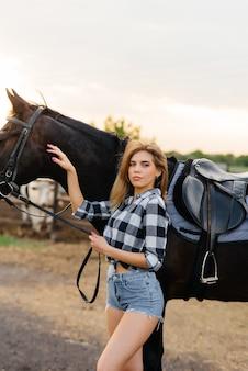 Een jonge mooie meisjesrijder poseert in de buurt van een volbloedhengst op een ranch. paardrijden, paardenraces.