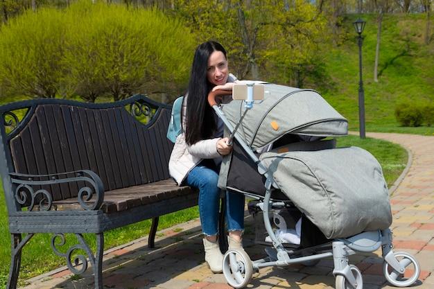 Een jonge mooie moeder, een meisje met donker haar, met een schattige baby in een kinderwagen, neemt een selfie van de telefoon.