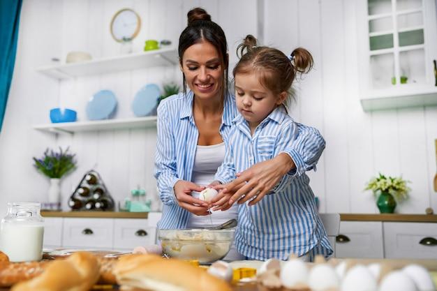 Een jonge mooie moeder en haar schattige dochter staat in de keuken aan tafel en wil een ei breken.