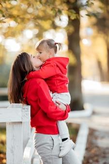 Een jonge mooie moeder houdt haar schattige dochtertje in haar handen tijdens een wandeling in het herfstpark