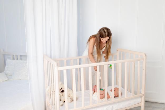 Een jonge, mooie moeder legt een baby van 6 maanden oud in een wieg, leunt eroverheen in de kinderkamer, moederdag, baby's ochtend