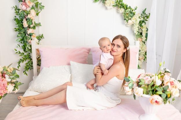 Een jonge mooie moeder met een 6 maanden oude dochter in haar armen zit op een wit bed in bloemen en knuffelt haar