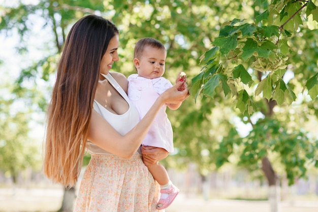 Een jonge mooie moeder met een dochtertje in de handen wandelen in het park. een vrolijke baby speelt met bladeren aan een boom.