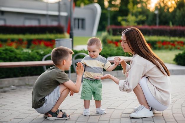 Een jonge mooie moeder met twee kleine jongens speelt in het park tijdens zonsondergang. gelukkige familiewandeling met kinderen in het park.
