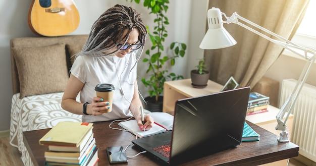 Een jonge mooie studente met dreadlocks studeert thuis op een laptop op een online les