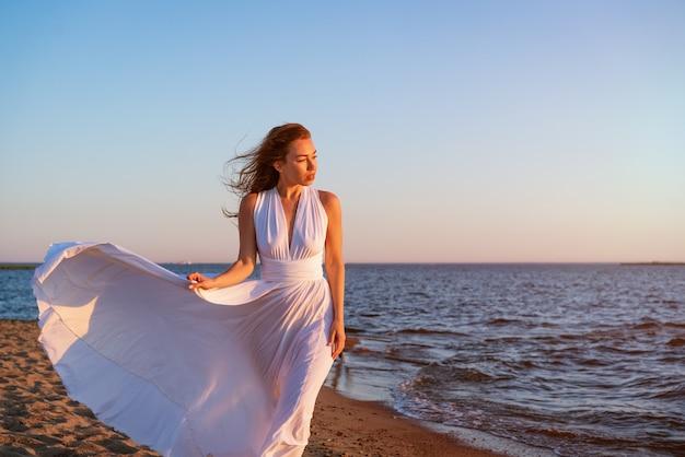 Een jonge mooie volwassen brunette vrouw in een witte wapperende jurk staat aan de zandige oever van de...