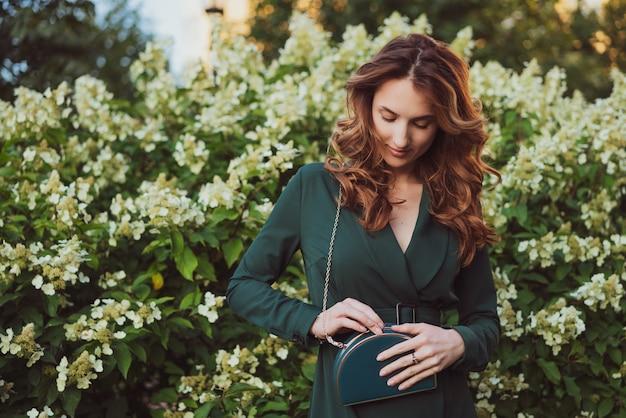 Een jonge mooie volwassen vrouw in een groene jurk staat tegen bloeiende struiken en heeft een kleine groene tas in haar handen