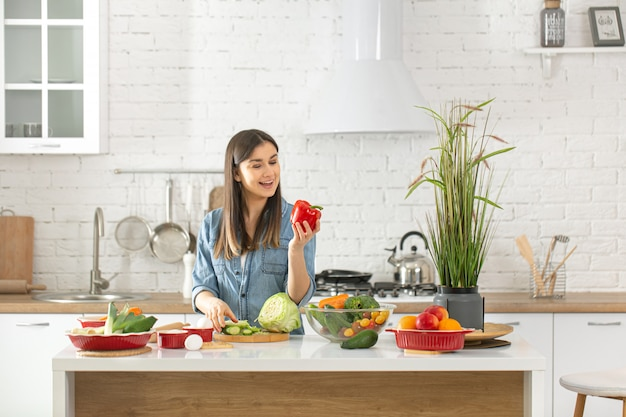 Een jonge mooie vrouw bereidt een salade van verschillende groenten in de keuken voor.