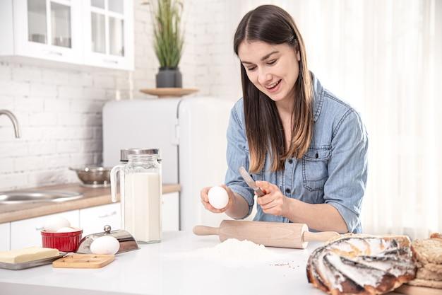 Een jonge mooie vrouw bereidt zelfgemaakte taarten in de keuken. het concept van goede, gezonde thuisvoeding.