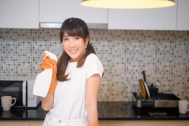 Een jonge mooie vrouw die beschermende rubberen handschoenen draagt, maakt de tafel in de keuken thuis schoon.