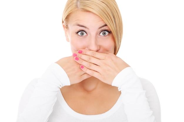 Een jonge mooie vrouw die haar lippen bedekt met handen op een witte achtergrond