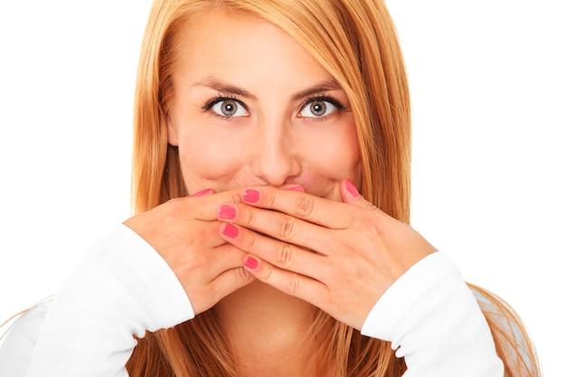 Een jonge mooie vrouw die haar lippen bedekt met handen over wit