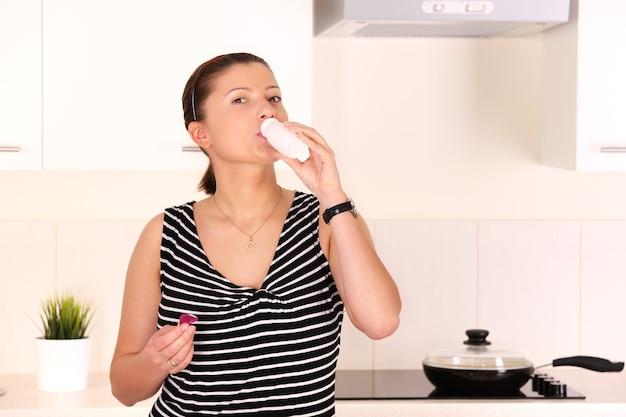 Een jonge mooie vrouw die melk drinkt in de keuken