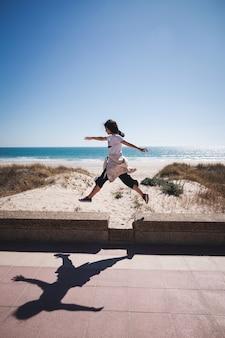 Een jonge mooie vrouw die met de armen en benen wijd open op het strand springt. grappige oefeningen doen op het strand