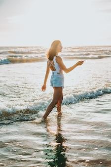 Een jonge mooie vrouw die overdag aan de kust loopt