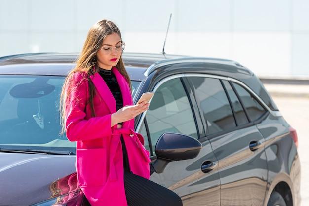 Een jonge, mooie vrouw die zich bij de auto bevindt en een tekstbericht op haar smartphone schrijft