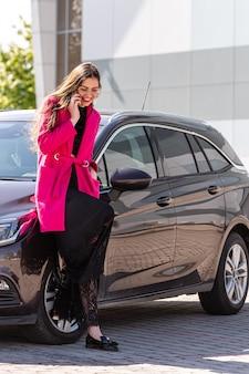 Een jonge, mooie vrouw die zich bij de auto bevindt en op de telefoon spreekt