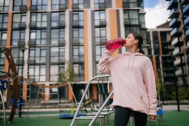 Een jonge mooie vrouw drinkt water op de speelplaats