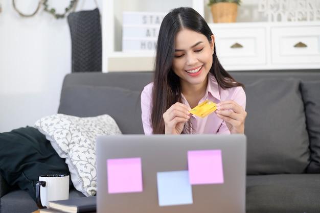 Een jonge mooie vrouw gebruikt creditcard voor online winkelen op internetwebsite thuis, e-commerce concept