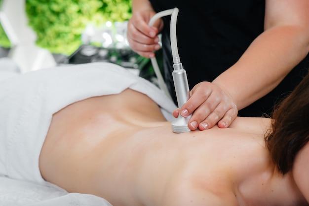 Een jonge mooie vrouw geniet van een professionele vacuümmassage in de spa