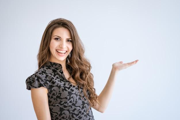 Een jonge mooie vrouw glimlachte en wees naar de zijkant