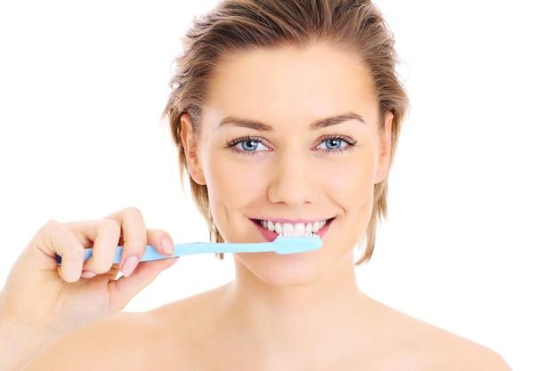 Een jonge mooie vrouw haar tanden poetsen op een witte achtergrond white
