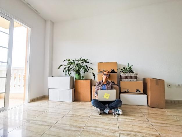 Een jonge mooie vrouw in een leeg huis met behulp van haar laptop met de dozen en packs