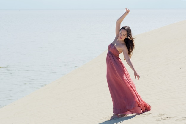 Een jonge mooie vrouw in een roze jurk loopt op de duinen