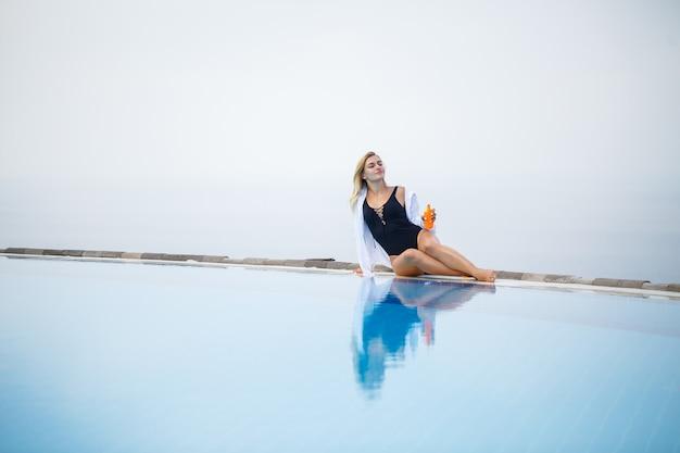 Een jonge mooie vrouw in een zwempak zit bij het zwembad en smeert haar huid in met zonnebrandcrème
