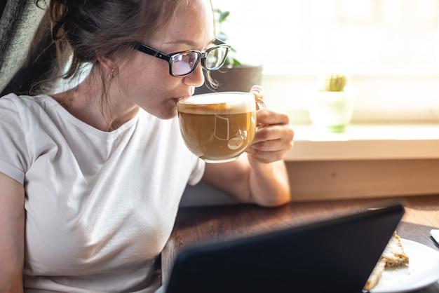 Een jonge mooie vrouw leest interessant nieuws op internet met behulp van een gadget-tablet zittend aan een tafel bij het raam