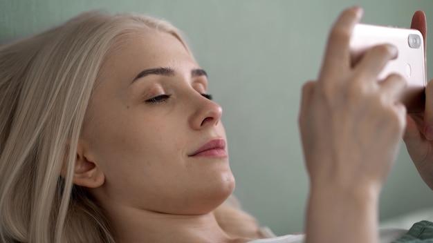 Een jonge mooie vrouw ligt op een bed met een telefoon in haar handen en kijkt naar het scherm. close-up, zijaanzicht. 4k uhd
