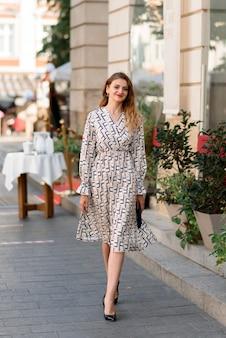Een jonge mooie vrouw loopt langs de straat in de stad.