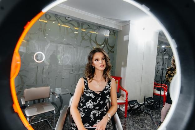 Een jonge mooie vrouw maakt een mooie avondmake-up voor de spiegel.