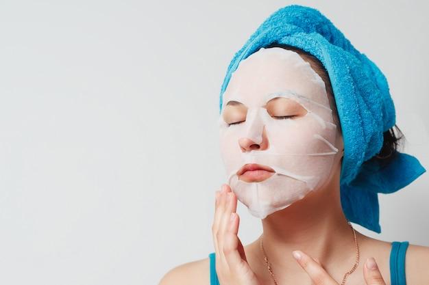 Een jonge mooie vrouw maakt gebruik van een stoffen cosmetisch gezichtsmasker met een handdoek om haar hoofd.