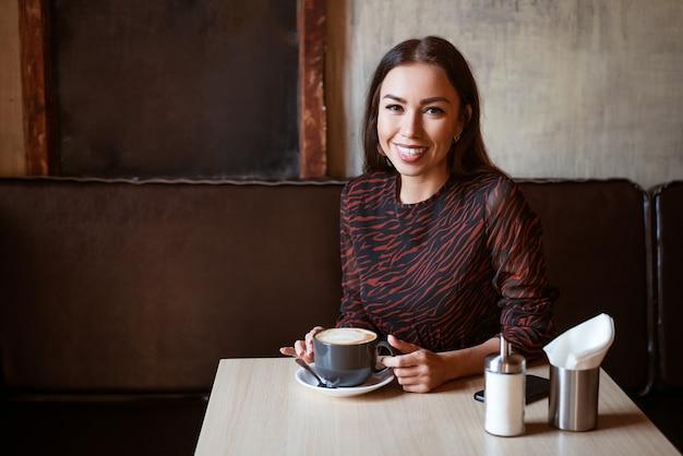 Een jonge mooie vrouw met donker haar kaukasisch uiterlijk met make-up in een bruine jurk zit aan een tafel in een café met koffie en lacht met een sneeuwwitte brede glimlach