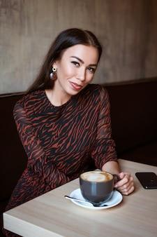 Een jonge mooie vrouw met donker haar kaukasisch uiterlijk met make-up in een bruine jurk zit ...