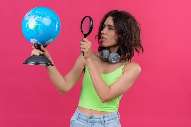 Een jonge mooie vrouw met kort haar in een groene crop top in koptelefoon kijken wereldbol aandachtig met vergrootglas