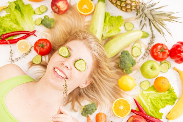 Een jonge mooie vrouw omringd door groenten en fruit