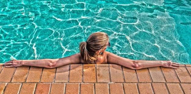 Een jonge mooie vrouw ontspant bij het zwembad. wellness concept. kuuroord en relax, vrouwelijk geluk.