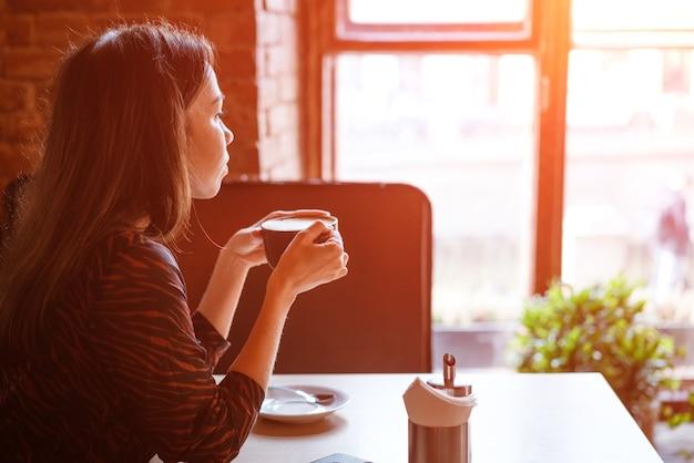 Een jonge mooie vrouw zit aan een tafel met een mok koffie bij het raam in een café, opzij kijkend met een peinzende blik
