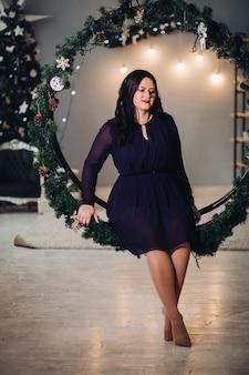 Een jonge mooie vrouw zit in een grote ronde kerstversiering gemaakt van sparren takken