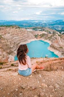 Een jonge mooie vrouw zit op de rand van een klif met steengroeve in de vorm van een hart