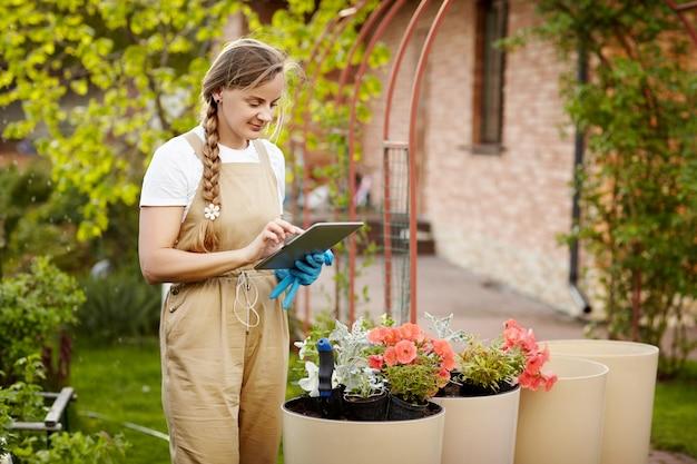 Een jonge mooie vrouwentuinman houdt een tablet voor nota's, controleerend de staat van bloemen.