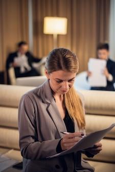 Een jonge mooie zakenvrouw gaat door haar toespraak in een hotelkamer met haar familie in de rug